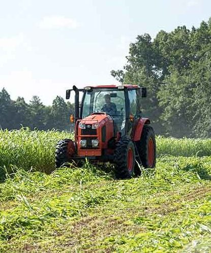A farmer harvesting crops in his tractor